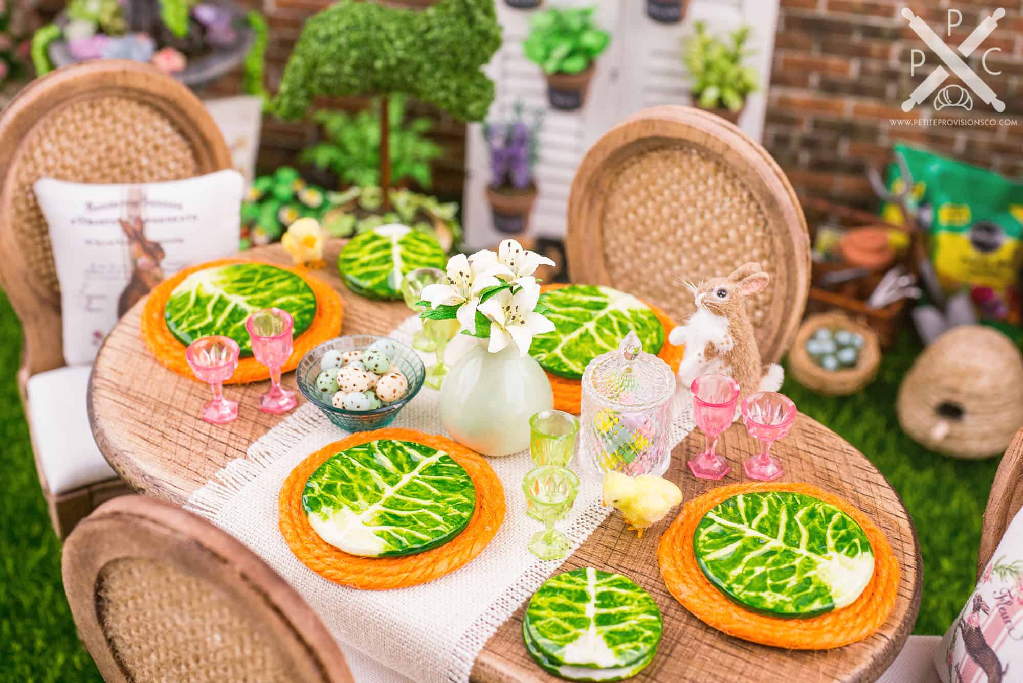 A dollhouse miniature spring, Easter table setting with cabbageware, pink and green glassware and white lilies by The Petite Provisions Co.