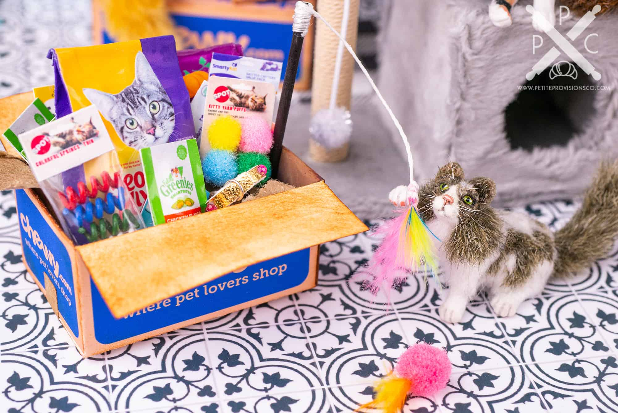1/12 scale cat with a box full of cat food and toys from Chewy in a dollhouse miniature scene by Erika Pitera, The Petite Provisions Co.