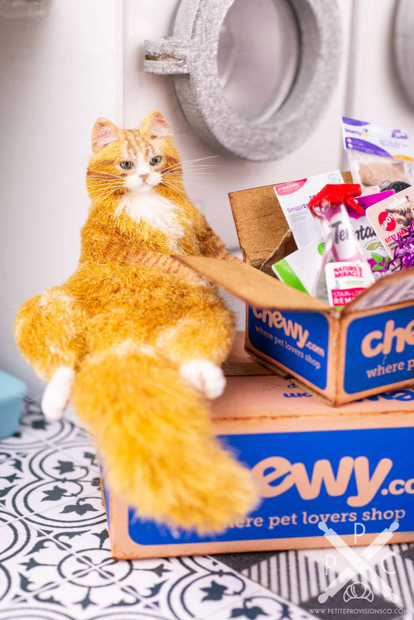 Dollhouse miniature fat orange tabby cat sitting on a cardboard box in a one inch scale scene by Erika Pitera, The Petite Provisions Co.