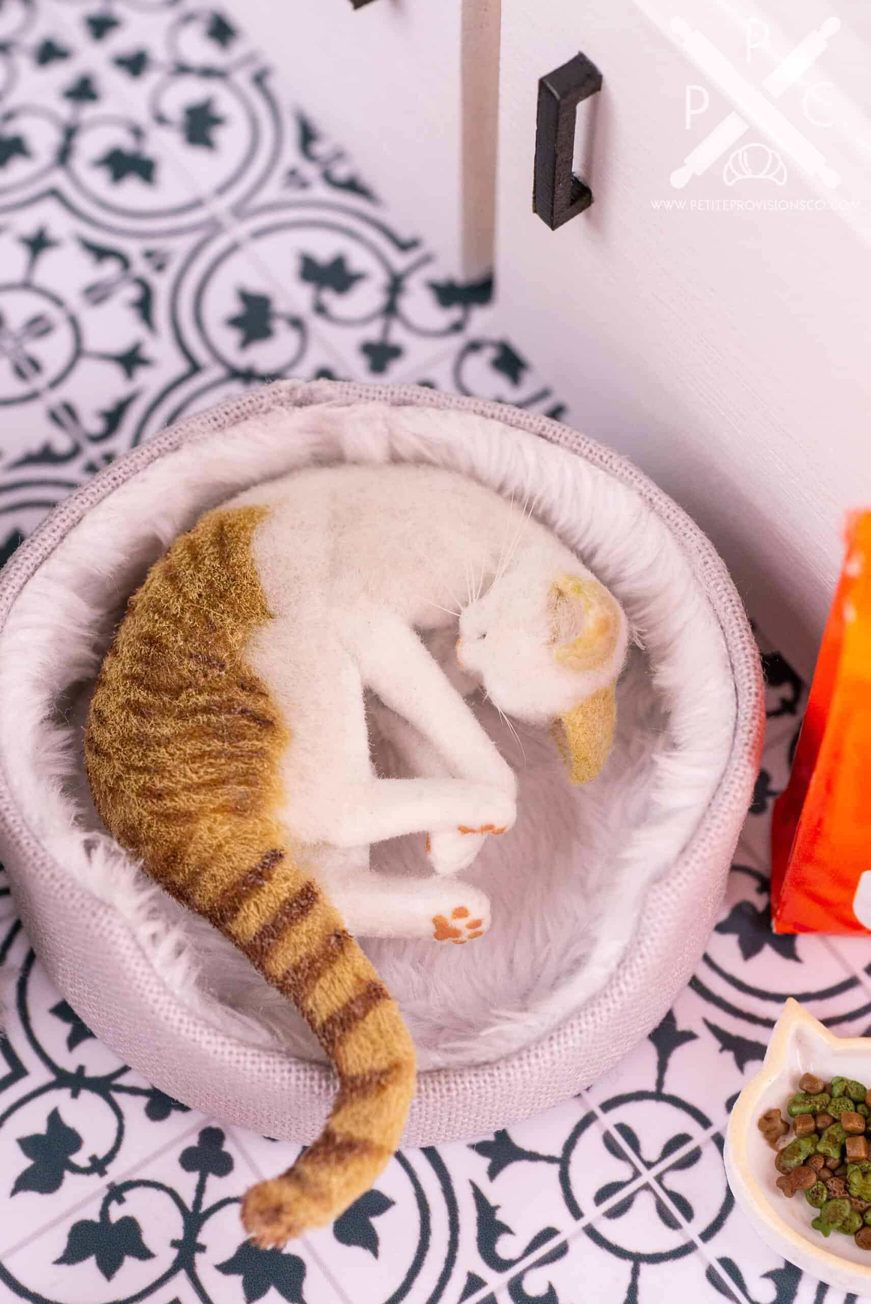 Dollhouse miniature cat sleeping in a handmade pet bed in a one inch scale scene by Erika Pitera, The Petite Provisions Co.
