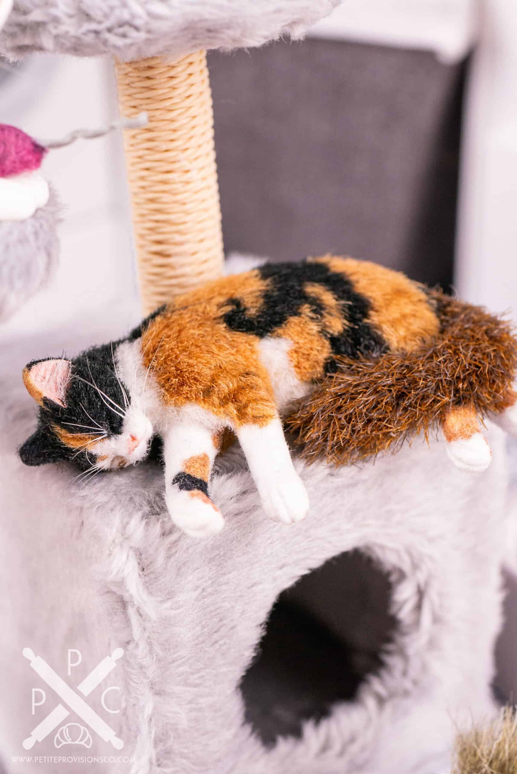One inch scale sleeping calico cat on a handmade cat tower in a dollhouse miniature scene by Erika Pitera, The Petite Provisions Co.