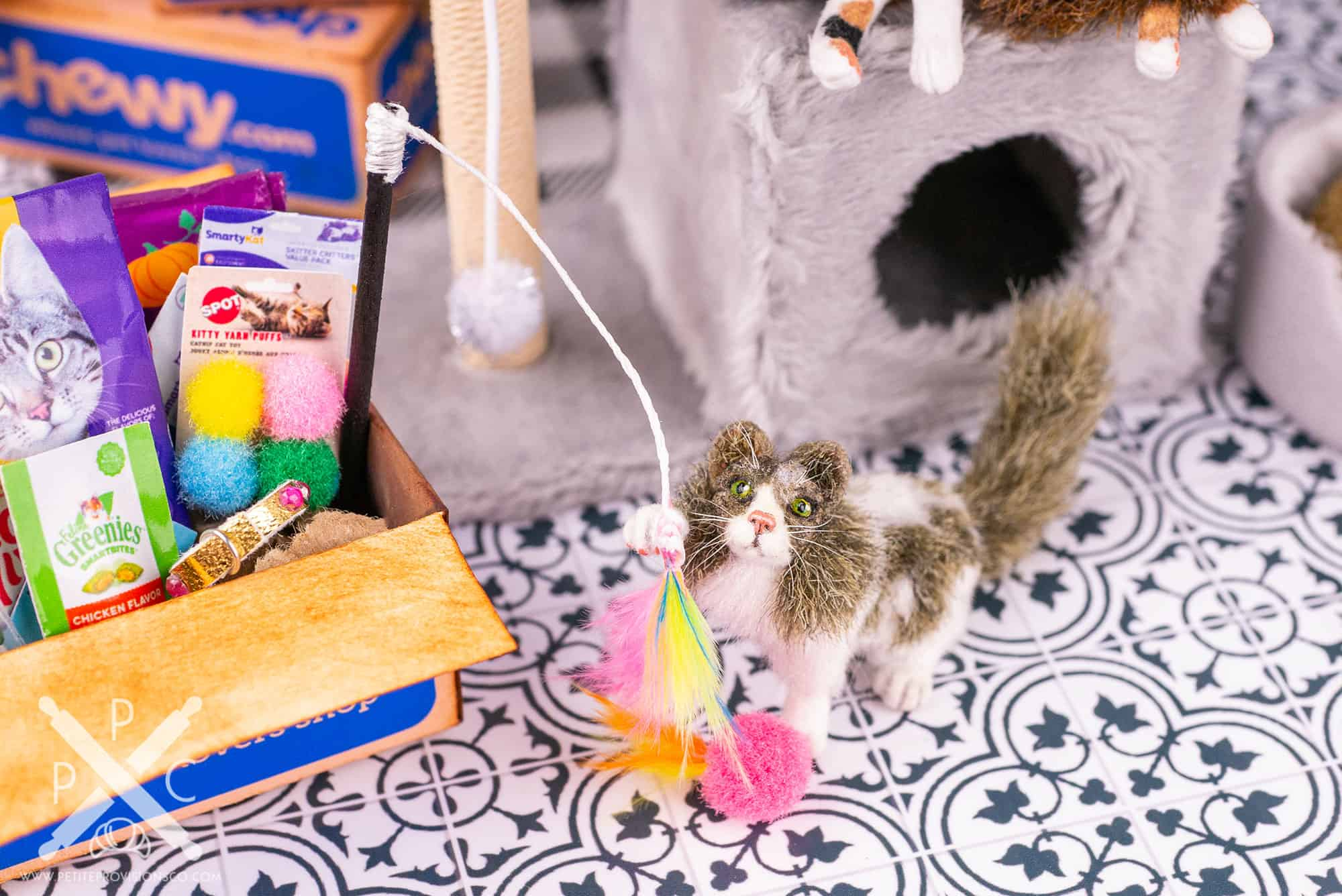 1/12 scale cat playing with a feather cat toy in a dollhouse miniature scene by Erika Pitera, The Petite Provisions Co.