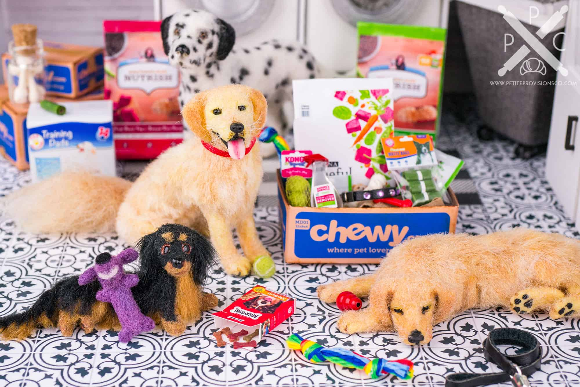 Dollhouse miniature dogs with shipping boxes of toys and food from Chewy in a one inch scale scene by Erika Pitera, The Petite Provisions Co.
