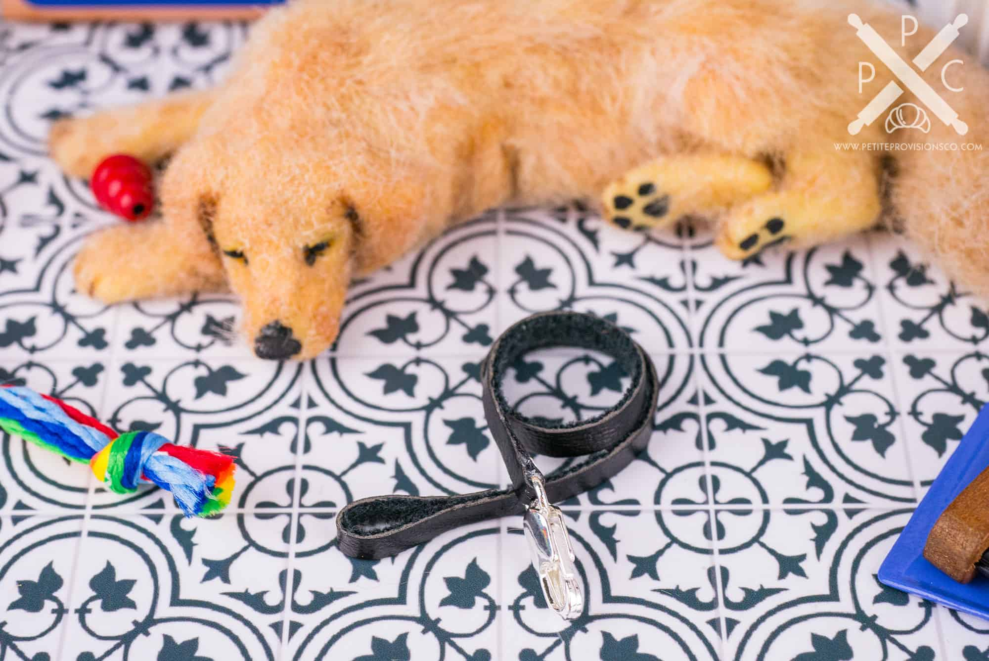 Handmade dollhouse miniature leather dog leash with a sleeping dog in a one inch scale scene by Erika Pitera, The Petite Provisions Co.