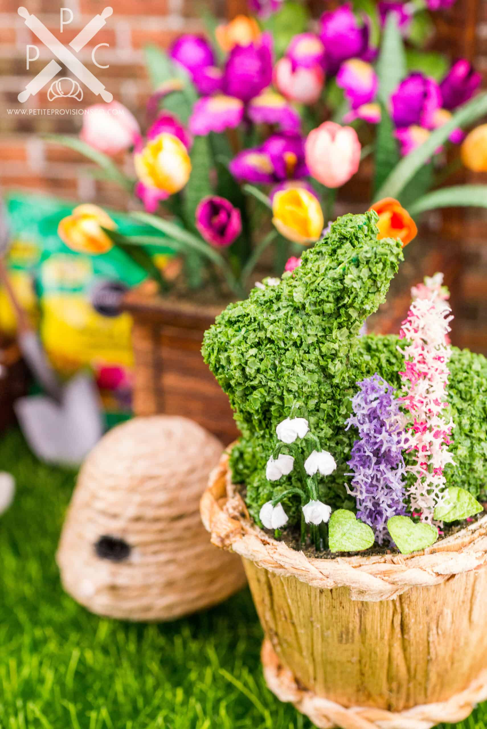 A dollhouse miniature bunny topiary in a planter with flowers by The Petite Provisions Co.