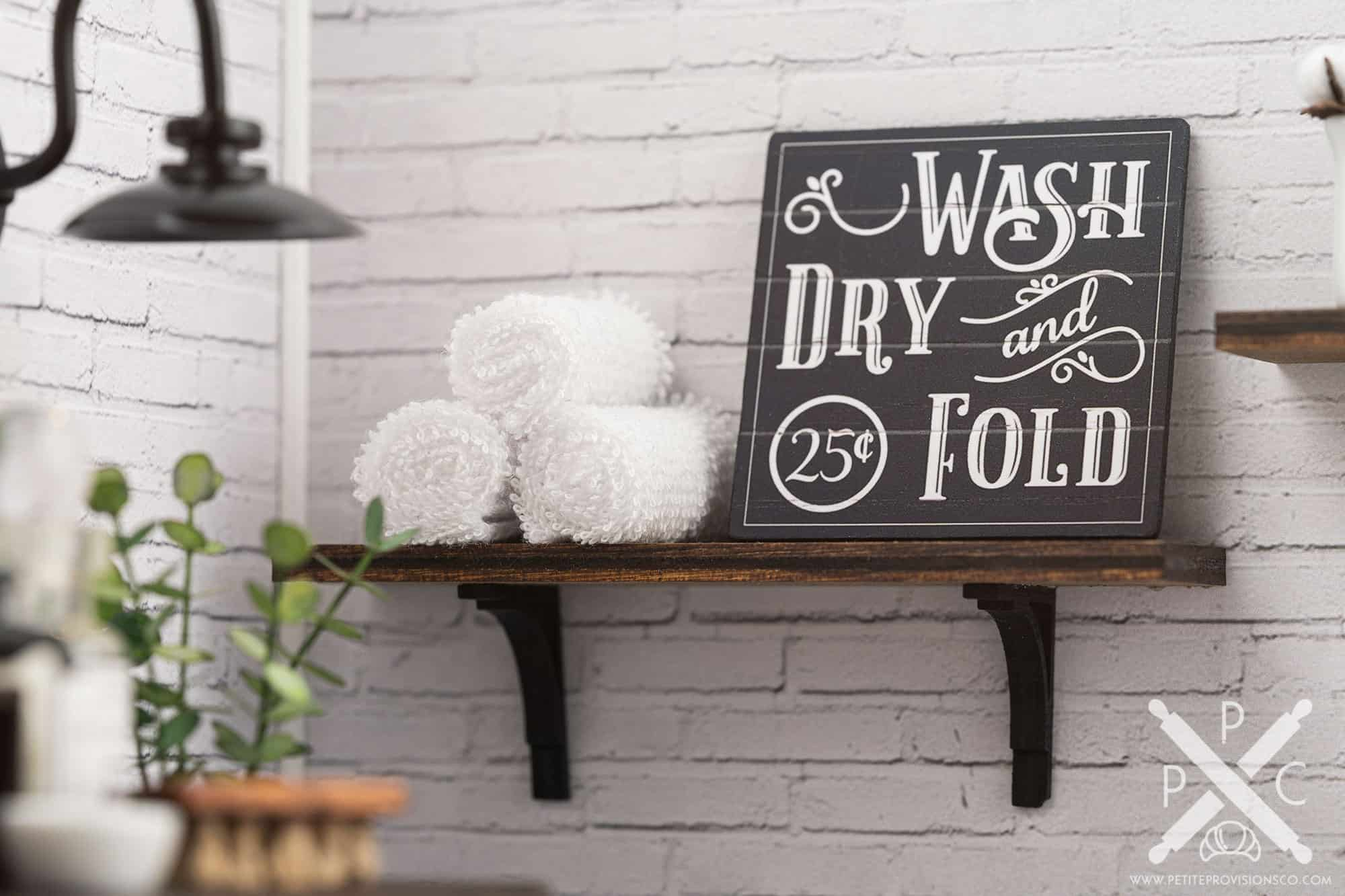 A wall shelf with towels and a laundry sign in a one-inch scale laundry room scene with farmhouse decor