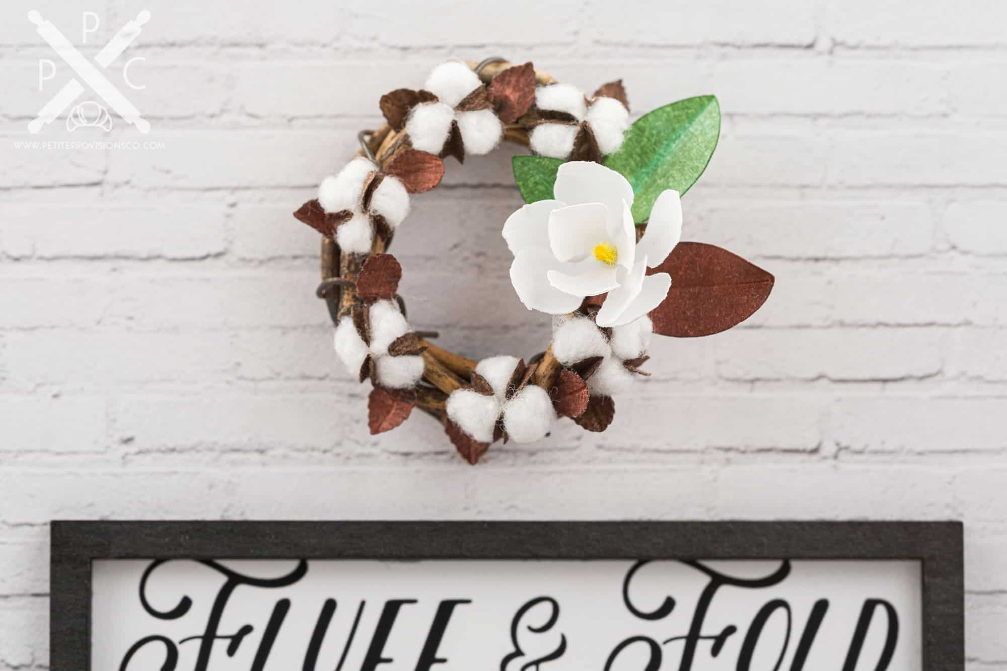 A handmade miniature wreath with cotton and magnolia in a one-inch scale laundry room scene with farmhouse decor