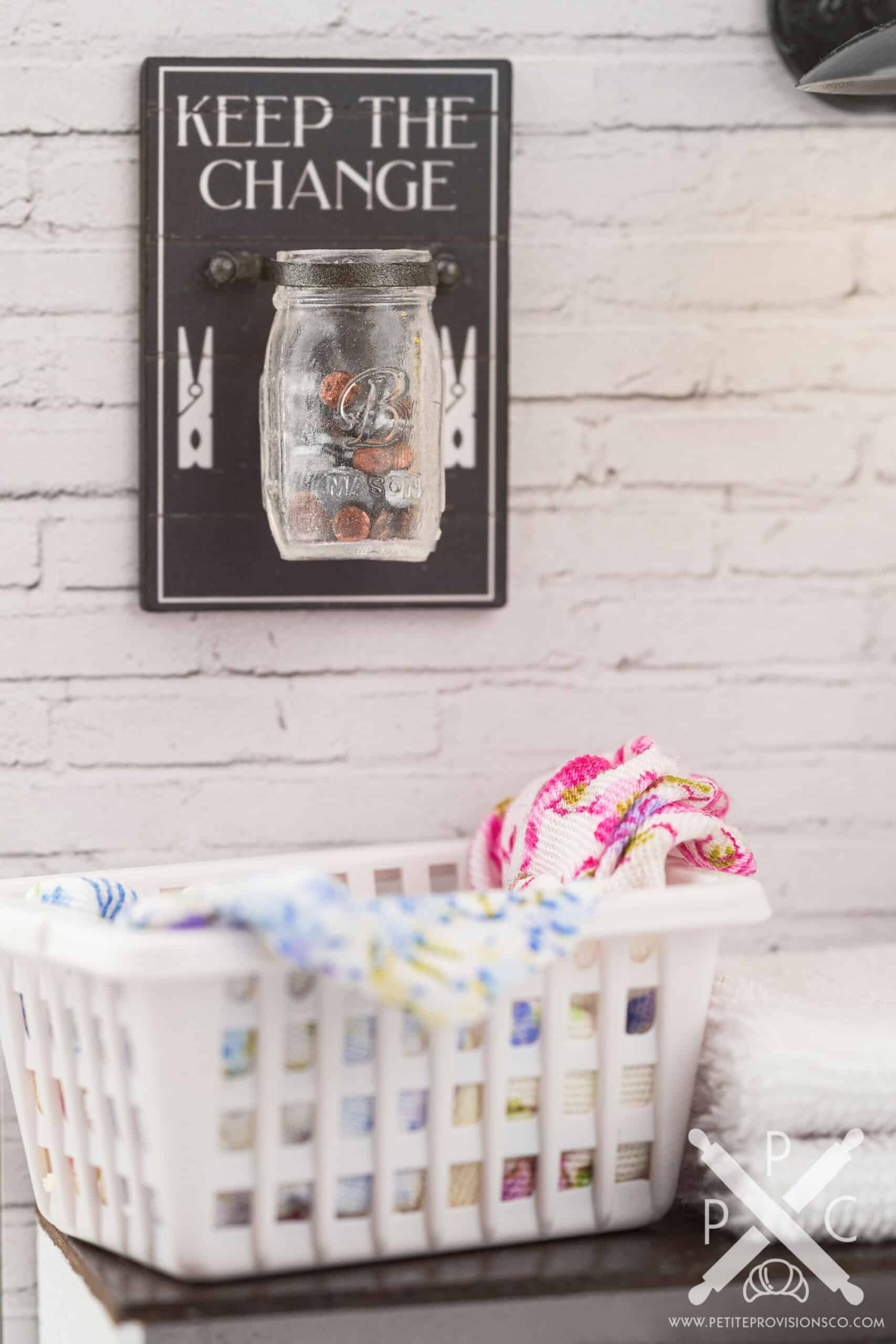 A dollhouse miniature keep the change jar of coins in a one-inch scale laundry room scene with farmhouse decor