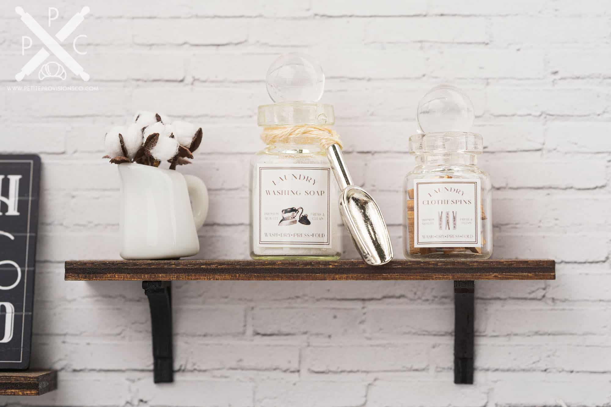 Handmade jars of laundry washing soap and clothespins in a one-inch scale laundry room scene with farmhouse decor