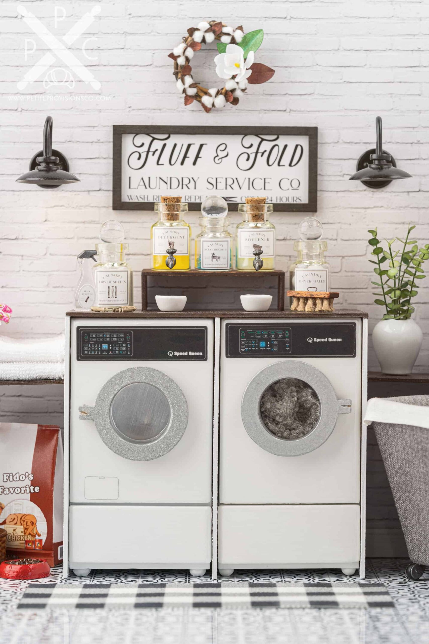 A washer and dryer set in a one-inch scale laundry room scene with farmhouse decor