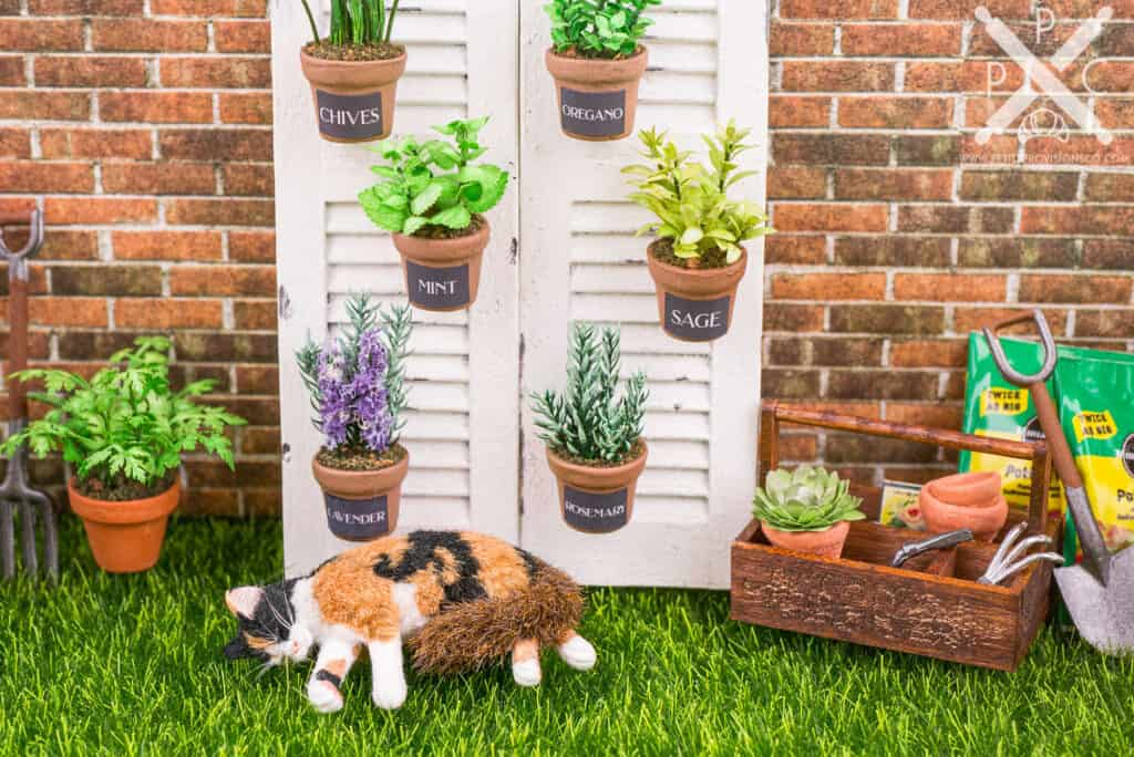 Dollhouse miniature herb garden with calico cat napping in the grass