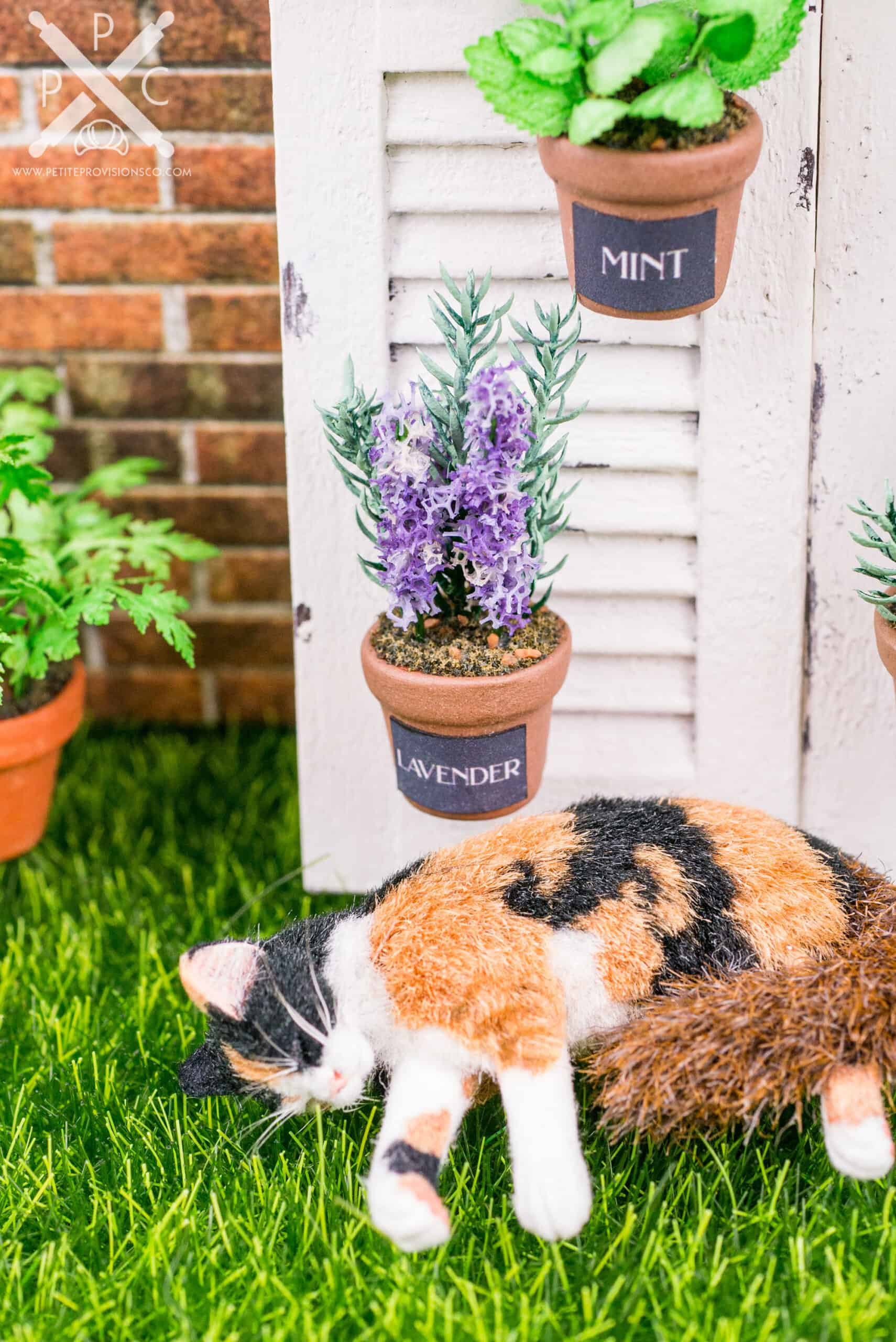 One inch scale potted lavender plant with calico cat napping